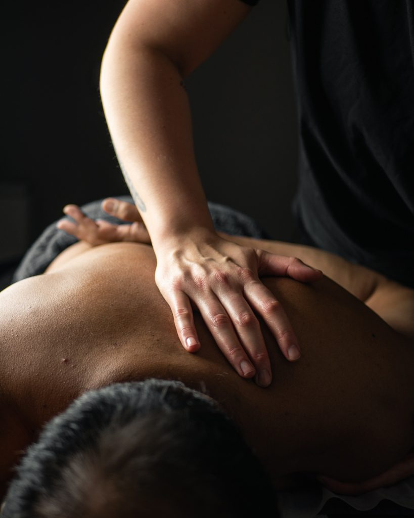 A person laying on a massage table and getting a massage by a man.